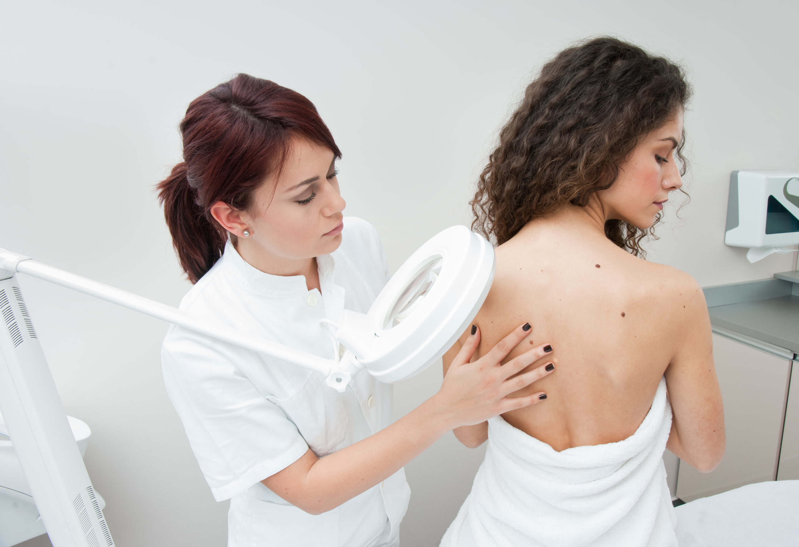 Доктор косметолог осматривает пациента